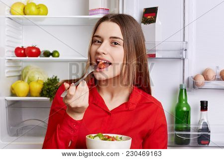 Cute Young Woman Tastes Delicious Fresh Vegeterian Salad, Keeps Fit, Poses In Kitchen Against Opened