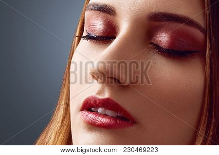 Close Up Shot Of Beautiful Female With Healthy Pure Skin, Keeps Eyes Shut, Demonstrates Nice Make Up