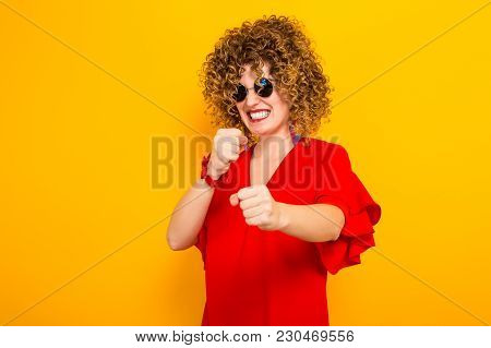 Portrait Of A White Woman With Afrro Curly Hairstyle In Red Dress And Sunglasses Holding Fists In Fr