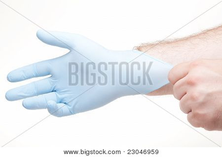 A Doctor Putting On A Latex Glove