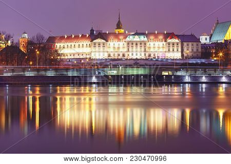 Royal Castle In Old Town With Reflection In The Vistula River During Evening Blue Hour, Warsaw, Pola