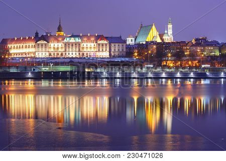 Old Town With Reflection In The Vistula River During Evening Blue Hour, Warsaw, Poland.