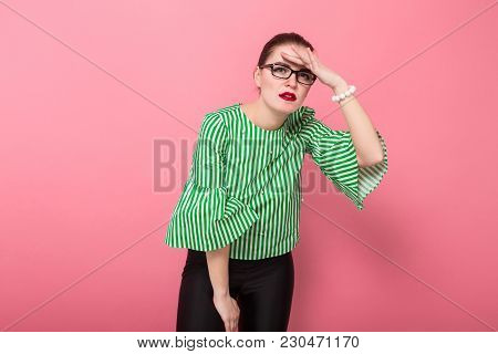 Portrait Of Attractive Businesswoman With Hair Bun In Striped Blouse And Eyeglasses Holding Her Fore