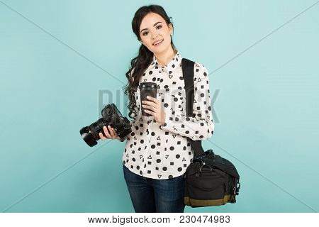 Portrait Of Young Attractive Woman Photographer In White Shirt Holding Camera And Drinking Take-away