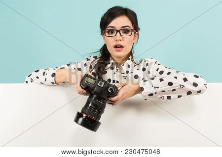 Portrait Of Young Attractive Surprised Woman Photographer In White Shirt Holding Camera Over White B