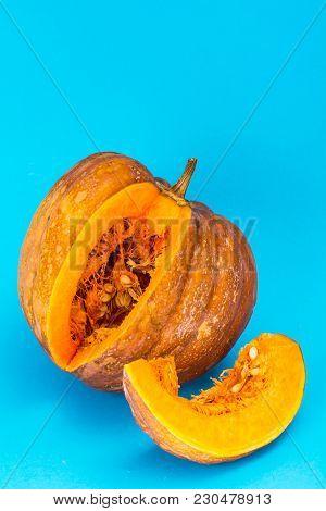Sliced Ripe Pumpkin On Blue Wooden Table. Studio Photo