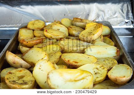 Hot Baked Seasoned Halved Potatoes On Trey Cooked In Oil. Street Food. Appetizing Golden Crust. City