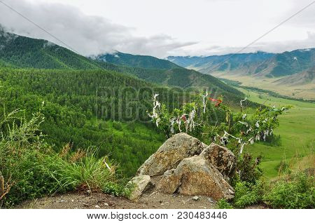 Stone And Bush, Hung With Ribbons Against The Landscape Of A Mountain Valley. Chike-taman Road Pass,