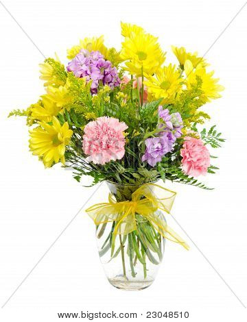 Colorful flower arrangement centerpiece in glass vase with carnations, daisies isolated on white