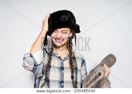 Beautiful Laughing Girl From Russia In A Warm Fur Hat Holds Gray Winter Boots