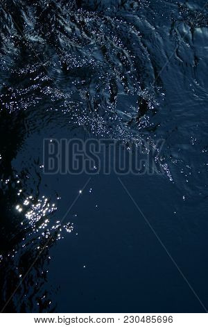A Dark Blue Texture Of Light Playing On The Ripples Of Water.