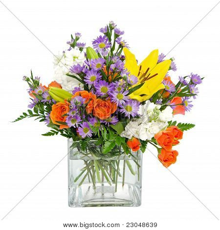 Colorful flower arrangement centerpiece in square glass vase with roses, daisies and llilies