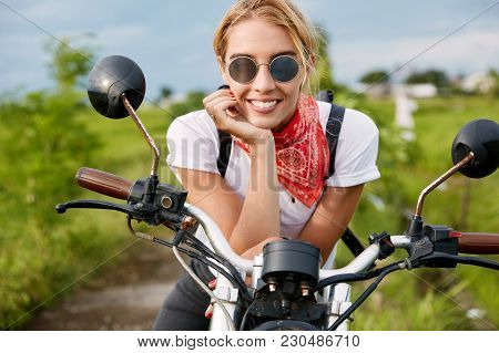 Outdoor Shot Of Positive Active Female Driver Sits On Fast Motorbike, Wears Fashionable Clothing, Ha