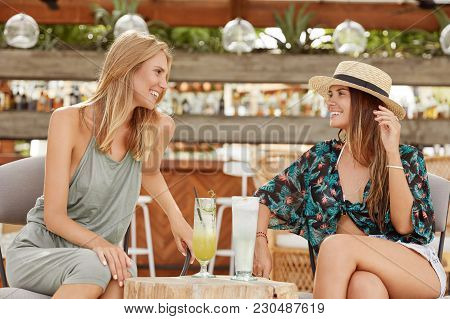 Two Female Friends Spend Spare Time In Cozy Bar, Dressed In Summer Clothing As Going On Beach, Drink