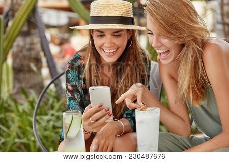 Cropped Shot Of Overjoyed Females Recreat Together At Outdoor Cafe In Tropical Country, Look Joyfull