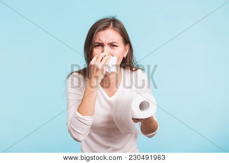 Young Woman With Handkerchief. Sick Girl Isolated Has Runny Nose On Blue Background.
