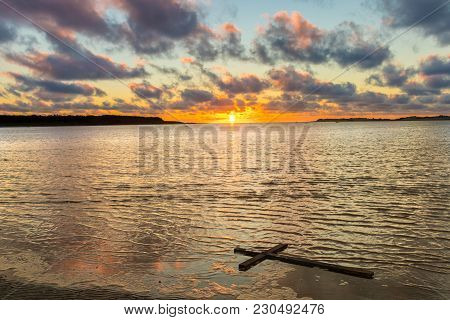Bay Of Water With One Black Cross Floating In It As The Sunsets.