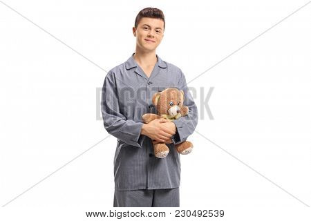 Teenage boy in pajamas holding a teddy bear isolated on white background