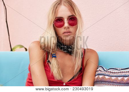 Adorable Blonde Young Woman Wears Red Shades, Looks Seriously In Camera, Enjoys Good Rest In Public