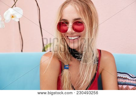 Close Up Shot Of Happy Young Blonde Woman Wears Sunglasses, Has Broad Smile And White Even Teeth, Dr