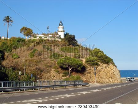 Lighthouse On A Mountain And Road Beside Sea