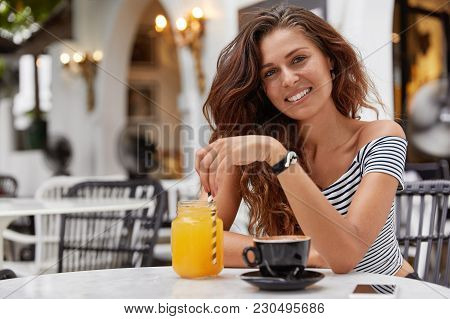 Positive Adorable Young Woman With Dark Wavy Hair, Recreats Alone At Cafeteria With Various Beverage
