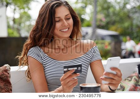 Photo Of Beautiful Female Tourist Uses Modern Smat Phone And Credit Card For Booking Ticket Online T