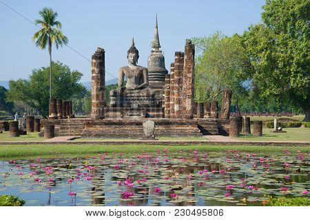View Of The Sculpture Of A Seated Buddha. Ruins Of The Temple Of Wat Chana Songkram In The Historica