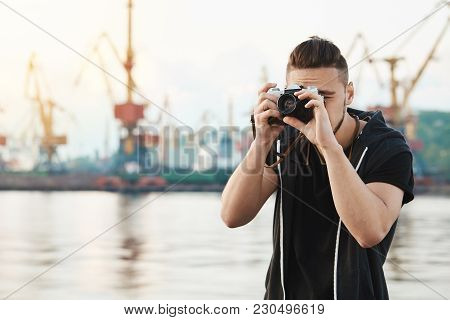 Attractive Guy Working With Camera. Young Stylish Photographer Looking Through Camera During Photo S