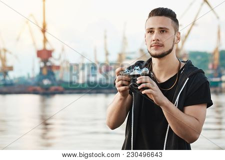 When Hobby Becomes Beloved Work. Portrait Of Dreamy Creative Young Guy With Beard Holding Camera And