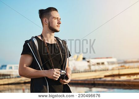 Outdoor Shot Of Young Good-looking Male Photographer Standing In Harbour Looking How Sunset Reflects