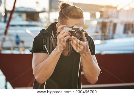 Cameraman Trying Hold Still Not To Scare Birds. Portrait Of Focused Young Male Photographer Looking