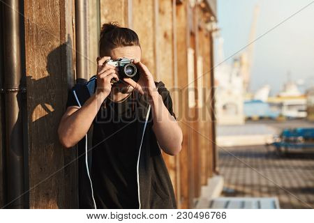 Capturing Every Moment Of Life. Outdoor Shot Of Young Stylish Photographer Looking Through Vintage C