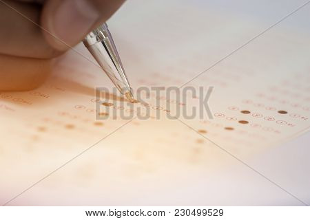 Education Test Concept : Hands Student Holding Silver Pen For Testing Exams Writing Answer Sheet Or