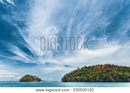 Spectacular cloudy blue sky over the calm ocean and limestone cliffs. Thailand. Ideal background for the various kinds of the sky space and marine collages and illustrations.