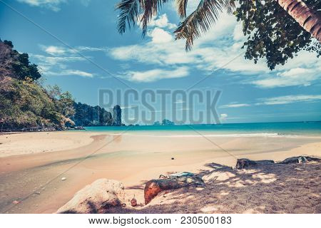 Breathtaking scenery the sand shore of the crystal clear warm ocean, limestone cliffs and tropical plants of the exotic island, the Kingdom of Thailand. Perfect place for paradise rest and relaxation.