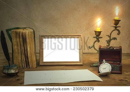 The Letter. Empty Photo Frame With Copy Space, Book And Burning Candle In Vintage Candlestick Feathe