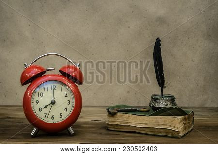 Old Book Retro Red Alarm Clock And Feather Pen With Inkpot And Rusty Key On Retro Wooden Table Backg
