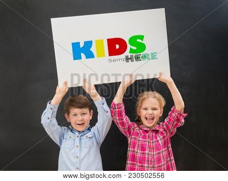 two little children keeping blank paper sheet above their heads
