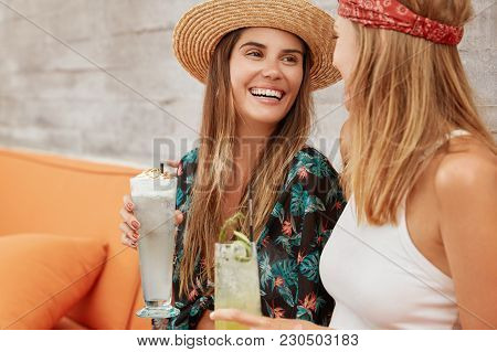 Portrait Of Happy Best Female Friends Have Pleasant Talk During Summer Party, Drink Exotic Fresh Coc