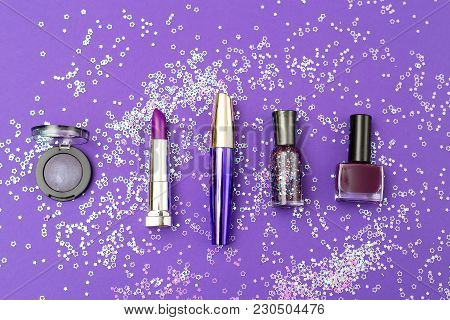 Violet Cosmetics On An Ultra Violet Background With Sequins In One Row. Flat Lay