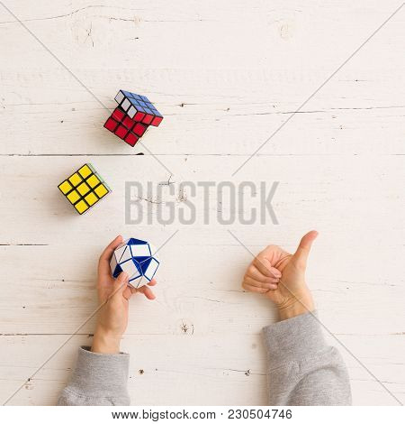 Moscow, Russia, February 16 2018: Rubik's Cubes And Snake Puzzle And Woman's Hands, Closeup, White W