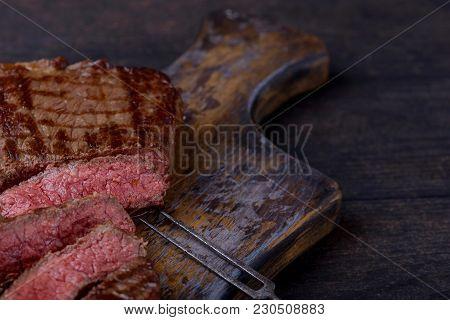 Closeup Sliced Medium Rare Steak On Cutting Board And Wooden Background