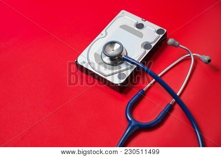 Stethoscope And Hard Disk Drive On Red Background. Computer Hardware Diagnostic And Repair Concept