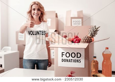 It Is Ok. Pretty Woman Keeping Smile On Her Face And Standing Near Food Box While Looking Straight A
