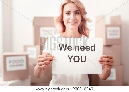 We Need You. Positive Delighted Woman Keeping Smile On Her Face And Raising Hands While Looking Forw