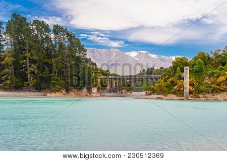 Bridge over river Rakaia with a view at Southern Alps peaks, turquoise river and blooming yellow gorse