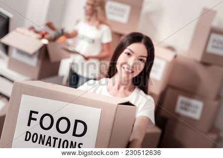 Preparing Parcel. Kind Female Person Working In Charity Community, Demonstrating Food Donations Whil