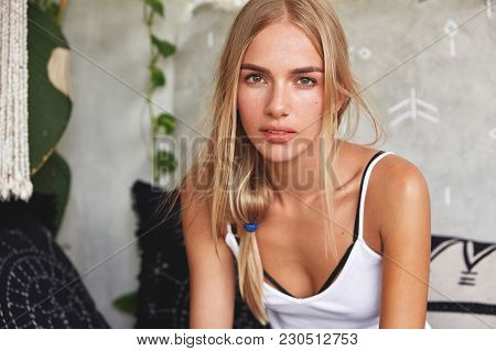 Blonde Gorgeous Female Model With Serious Expression, Dressed Casually, Sits On Sofa In Living Room,