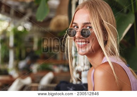 Happy Blonde Female Wears Trendy Sunglasses, Looks Positively Into Camera, Demonstrates White Perfec